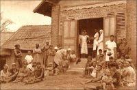 Minlaba, le dispensaire. - L'effort sanitaire colonial au Cameroun porte avant tout sur la lutte contre la maladie du sommeil. L'affection, endémique dans la région, a en effet pris un tour épidémique catastrophique à la fin du XIX ème siècle, avec la circulation des populations engendrée par la pénétration coloniale et par les mouvements de main d'œuvre, vers les plantations notamment. En quelques décennies, la trypanosomiase emporte plusieurs millions de personnes, dans une hécatombe restée sans équivalent. Du temps de leur occupation, les Allemands prennent la mesure du problème et ébauchent un dispositif, essentiellement basé sur la concentration des malades dans des sites dédiés ou, pour le moins, en préparant des lieux d'accueil. Les Français reprennent l'idée à leur compte, mais en la sophistiquant selon les principes établis par Eugène Jamot, le maitre de la lutte contre la maladie du sommeil. Ils consistent à débusquer manu militari les patients dans les villages grâce à des équipes mobiles, à traiter les moins atteints dans les dispensaires et les postes de santé avancés –auxquels sont également dévolus les soins courants pour les autres affections- et à transporter les plus malades dans des « hypnoseries », établissements spécialisés dans leur traitement. Voici la description d'un de ces postes avancés, faite au milieu des années trente : « Les hôpitaux sont supplées, pour les cas bénins, par des infirmeries de brousse. Une case à trois compartiments, dont l'un sert de chambre à l'infirmier. Des thermomètres, des compresses, des bandes, des seringues, une armoire à médicaments, d'où l'on a exclu les poisons qu'on ne confierai pas sans péril à un indigène même diplômé. C'est tout. C'est déjà beaucoup ». Source : J. Wilbois Le Cameroun, éditions Payot, Paris, 1934.