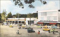 Yaoundé, place de la cathédrale, le magasin Printania. – En 1958, le « Printania » de Yaoundé est la seconde grande surface à ouvrir au Cameroun, un an après le Monoprix de Douala et un avant le Printania de cette même ville. Cette enseigne a été créée en 1952, par un pilier de la distribution en Afrique, la SCOA (Société commerciale de l'Ouest Africain), en association avec Le Printemps. Pour dynamiser le commerce dans les capitales d'AOF et d'AEF, cette même société lance également une autre chaine avec le groupe Prisunic, les magasins « Pariscoa ». Cette formule moderne s'adresse en premier lieu à la clientèle européenne des villes, laissant celle des Africains et des « broussards » aux comptoirs, forme traditionnelle du commerce colonial. Le Cameroun connait en la matière un certain dynamisme, avec une intense concurrence entre sociétés commerciales françaises, anglaises et allemandes notamment. Le statut de tutelle sous mandat de la SDN puis de l'ONU implique, en effet, l'égalité des Etats membres et interdit d'établir des tarifs douaniers préférentiels.