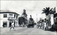 Douala, carrefour avenue Poincaré et rue du 27 août. – « Le voyageur qui débarque pour la première fois à Douala est surpris de se trouver devant un vaste chantier […]. Dans les rues – goudronnées depuis peu – le mouvement des automobiles et bicyclettes devient tel que le service de la circulation a dû installer aux principaux carrefours des « clignotants » vert et rouge, les agents, les « polices » comme on les appelle ici, ne parvenant plus, par leurs seuls moyens individuels, bâton et sifflet, à éviter, aux heures d'affluence, des embouteillages spectaculaires ». Sources : « Douala, porte du Cameroun » (brochure), Douala, Secrétariat social du Cameroun et Chambre de commerce, d'agriculture et d'industrie du Cameroun, 1953.