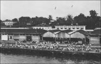 Douala, un coin des quais. - « Le port de Douala, avec balises, chenal et quais. On les a construits sur du poto-poto. Les paquebots y accostent. Seuls ceux qui ont débarqué des passagers ou chargé des marchandises en face des wharfs ou à travers la barre des côtes africaines, savent ce que c'est qu'un quai. » (1). « Des dragages ont été effectués aux postes de mouillage qui peuvent recevoir des navires de 150 mètres de long. Devant la ville il existe 5 postes que peuvent prendre les navires ne désirant pas accoster à quai. On peut aussi mouiller en amont des quais. Les quais ont une longueur de 550 mètres avec des profondeurs au pied de 7 à 10 mètres ; ils bordent a ville et permettent l'accostage de 4 grands bâtiments. En amont le quai dit, du chalandage, où les profondeurs sont de 1 à 3 mètres, prolonge les quais précédents » (2). Sources : (1) J. Wilbois Le Cameroun, éditions Payot, Paris, 1934. (2) Instructions nautiques – Côtes Ouest d'Afrique, Paris, Service Hydrographique de la Marine, 1941.