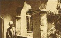 Le sultan de Foumban sur la galerie de son palais. – Dernier représentant de l'empire Bamoun, l'un des plus anciens du continent, le sultan de Foumban embarrasse les  autorités mandataires françaises - cette partie du Cameroun est placée en 1922 sous mandat français par la Société des Nations. Elles vont s'employer à réduire son pouvoir et son emprise, en transformant l'empire en simple région dès 1922, puis l'année suivante, en simple subdivision de la circonscription de Dschang. La même année, le souverain Njoya est déposé. Exilé à Mantoun dans un premier temps, puis à Yaoundé, il meurt en 1933, scellant la disparition de l'organisation politique Bamoun et la suprématie de l'administration coloniale française. – Ce cliché fait partie de l'œuvre du photographe Georges Goethe. Né en 1897 en Sierra Leone, il vient au Cameroun  en 1922 comme agent commercial et, fasciné par les hommes, les villes et les paysages, se lance en amateur dans la photographie. Pionnier du genre, il acquiert vite une réputation, et les chefs de villages le demandent. En 1931, il devient professionnel et ouvre à Douala son studio, appelé « Photo Georges », où seront formés nombre des premiers photographes camerounais. Ses archives constituent un fonds d'une grande richesse sur la vie du pays. Depuis sa disparition  en 1976, son fils, Doualla Cyrille Goethe, poursuit son oeuvre.