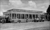 Foumban, le tribunal. – La ville de Foumban, capitale du royaume Bamoun, est le siège du pouvoir de cet empire parmi les plus anciens d'Afrique. Les autorités mandataires françaises (cette partie du Cameroun est placée en 1922 sous mandat français par la Société des Nations) vont s'employer à réduire l'emprise du sultan du Bamoun. Ainsi, Foumban devient une simple région dès 1922, puis l'année suivante une subdivision de la circonscription de Dschang. La même année, le souverain Njoya est déposé.  Exilé à Mantoun dans un premier temps,  puis à Yaoundé, il meurt en 1933, scellant la disparition de l'organisation politique Bamoun et la suprématie de l'administration française. L'affluence au tribunal, sur cette photo qui date des années 1950, en est le symbole.