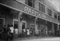 Douala, magasin Pariscoa (photo A. Gouelle).  – A la recherche d'une formule susceptible de rénover le commerce dans les capitales africaines, de type « grands magasins » et se démarquant des comptoirs, la SCOA (Société commerciale de l'Ouest Africain) s'associe à partir de 1952 avec le groupe Prisunic pour lancer une  chaîne de magasins sous l'enseigne Pariscoa et avec le groupe du Printemps pour ouvrir des magasins Printania. – « La clientèle européenne suffirait à elle seule à faire vivre un certain nombre de commerces (5 à 6000 Européens à Douala, sans compter les « broussards » qui viennent s'y ravitailler) ; la formule ancienne – comptoirs ou boutiques grecques – cherchant à convenir à la fois aux Européens et aux Africains, dont les goûts et les besoins sont souvent différents, semble condamnée à disparaître ». Source : « Douala, porte du Cameroun » (brochure), Douala, Secrétariat social du Cameroun et Chambre de commerce, d'agriculture et d'industrie du Cameroun, 1953.