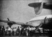 Arrivée de l'avion d'Air France à Douala, en 1950. – « Le camp d'aviation, son bar plutôt, est un des rendez-vous où l'on papote, les arrivées et les départs d'avions fournissant des sujets de conversation inépuisables » (1). Pour se rendre au Cameroun en 1950, les voyageurs doivent posséder un passeport, doivent avoir reçu les vaccinations antiamaryle et antivariolique. De plus, ils doivent verser une caution, ou produire une dispense délivrée par la Sûreté du territoire à la demande de l'employeur. Le montant de la caution s'élève à 30  000 francs CFA pour les Français, Belges, Allemands, Espagnols, Hollandais, Italiens, Luxembourgeois, Portugais et Suisses, à 50 000 f. CFA pour les Russes et Américains du Nord et du Sud, à 10 000 f. CFA pour les « Originaires de la Côte d'Afrique », et 40 000 f. CFA pour les autres nationalités. Les voyageurs doivent aussi disposer d'une autorisation d'embarquement, délivrée par la Délégation du Cameroun en France. Les vols d'Air France entre  Paris et Douala par Constellation durent 14 heures, avec une escale à Alger, et le billet coûte 57 800 f. CFA (115 600 francs métropolitains). Les vols UAT, sur DC4, passent par Alger et Niamey, et durent 18 heures comme les vols TAI qui passent par Alger et Kano, et le billet coûte sur ces compagnies 46 500 f. CFA, soit 93 000 f. métropolitains. Par comparaison, le SMIG (salaire minimal interprofessionnel garanti) créé en France en 1950, ne s'élevait alors qu'à 64 francs métropolitains par mois !  Source : « Douala, porte du Cameroun » (brochure), Douala, Secrétariat social du Cameroun et Chambre de commerce, d'agriculture et d'industrie du Cameroun, 1951.