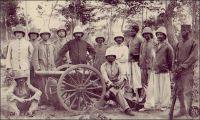 Section d'artillerie de la colonne de répression des N'gbans. - Le groupe des N'gbans, un des plus importants de la grande famille des Baoulés, ne se montre pas très accueillant face à l'entreprise coloniale. « Indépendants, braves, tenaces, chasseurs adroits et infatigables, confiants dans leurs forêts et fourrés impénétrables,[…]ils se sont toujours montrés adversaires redoutables et n'ont jamais voulu s'avouer complètement vaincus. Dès nos premières tentatives de pénétration en Côte d'Ivoire, ils opposent, à Singrobo, une résistance opiniâtre à la colonne Monteil; en 1902 et 1903, ils font subir des pertes nombreuses aux petites colonnes chargées de les punir des attaques qu'ils ont dirigées contre les convois de la ligne d'étapes ; ces colonnes terminées, mais non suivies du désarmement, ils ne payent pas l'amende de guerre qui leur a été infligée », explique Gabriel Angoulvant (1872-1932), le gouverneur général de Côte d'Ivoire de 1908 à 1916, à propos des actions de pacification menées à son initiative. Saisissant le prétexte de les désarmer –ils possèdent 2100 fusils, selon lui-, il envoie une colonne de tirailleurs solidement équipée, appuyée d'une artillerie légère, et parvient à soumettre la soixantaine de villages n'gbans entre avril et septembre 1910. Sources : Angoulvant, G., La pacification de la Côte d'Ivoire, Paris, éd. Emile Larose, 1916.