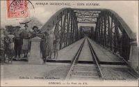 Dimbokro, le pont du N'zi. - Les travaux du chemin de fer « Abidjan-Niger » débutent en 1904. En 1909, le N'zi, une rivière, constitue la dernière grosse difficulté de la partie équatoriale du tracé ferroviaire ; il est franchi grâce à ce viaduc de 255 mètres de long. L'ouvrage et la gare de Dimbokro sont inaugurés le 11 septembre 1910, par le gouverneur général Angoulevant. La gare de Dimbokro reste le terminus du premier tronçon exploité, long de 181 km, jusqu'à l'ouverture en 1912 d'un nouveau tronçon de 135 km menant à Bouaké. Puis, entre 1919 et 1923, les 55 km séparant Bouaké de Katiola sont couverts. Entre 1924 et 1929 le tronçon Katiola-Ferkéssédougou, long de 187 km, est construit ; les 238 km supplémentaires, permettant de rallier Bobo-Dioulasso, sont achevés en 1932. La jonction ferroviaire entre Abidjan et Ouagadougou est réalisée en 1954. Enfin, du temps de la révolution Burkinabè (1983-1987), un réel effort populaire permet la construction d'un tronçon supplémentaire d'une centaine de kilomètres jusqu'à Kaya, à l'instigation de Thomas Sankara lui-même. Ce dernier tronçon n'a jamais été exploité. L'ambition était de joindre le gisement de manganèse de Tambao, à 200 km au nord de Kaya, sur lequel le pays fondait alors beaucoup d'espoirs.