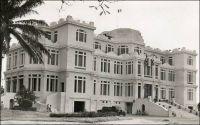 Abidjan, Palais du Gouvernement. – Ce palais rococo se dressait à l'emplacement de l'actuelle Présidence de la Côte d'Ivoire. Symbole du pouvoir colonial, il fut démoli après l'indépendance et remplacé par un bâtiment sans grand caractère. Sa construction avait été envisagée dès 1924, et pour la première fois on avait confié le projet à un cabinet d'architectes, Jaussely et Olivier qui était spécialisé dans l'architecture coloniale. Précédemment, la réalisation de tous les édifices officiels de Côte d'Ivoire était assurée par les Travaux Publics, un service de l'administration coloniale. Ce premier recours à une signature architecturale correspond à un revirement dans la politique antérieure du moins coûtant, tandis que cette colonie ne cesse de prospérer. Le chantier ne fut effectivement entamé qu'en 1931. Il avait finalement était confié à l'architecte Baudouin qui résidait à Abidjan. La construction, qui dura deux ans, ouvrait l'ère des grands travaux préparant le transfert de la capitale à Abidjan – elle se trouvait précédemment à Bingerville - en 1933. La richesse des décorations et installations du palais étaient alors inédite en Côte d'Ivoire.