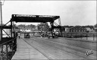 Abidjan, entrée du pont de Treichville. - Cet ouvrage un peu primitif - un pont flottant -, édifié en 1931, occupait approximativement l'emplacement de l'actuel pont Houphouët Boigny. Franchissant la lagune Ebrié, il reliait le quartier du Plateau, au nord, au quartier de Treichville au sud. Il fut détruit en 1957, pour céder la place au nouveau pont. Celui-ci, construit en béton précontraint sur des pieux profonds, comporte 8 travées pour une portée totale de 372 mètres. A la fin des années 1960, un autre pont, nommé pont Charles De Gaule fut édifié selon les mêmes techniques, à quelques centaines de mètres à l'est du pont Houphouët-Boigny, pour absorber une partie du trafic automobile en plein essor. Ce nouvel édifice, long de 592 mètres, est d'ailleurs dévolu à l'usage routier. Aujourd'hui, on annonce la construction prochaine d'un troisième pont sur la lagune Ebrié. Le nouvel ouvrage, qui portera le nom de l'actuel président de la république ivoirienne – au pouvoir depuis 2000 et maintenu dans ses fonctions par des accords internationaux en attendant que la situation militaire et politique permette l'organisation de nouvelles élections présidentielles –, reliera le quartier de Yopougon à l'île Boulay. Jusqu'à présent isolée, celle-ci constitue une vaste étendue proche du centre ville, disponible pour l'extension. Elle devrait accueillir de nouvelles infrastructures portuaires, une zone franche industrielle et commerciale, et un quartier d'affaires. Trois consortiums, un français, un italien et un allemand, sont en lice pour obtenir le chantier de ce pont.