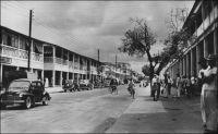 Abidjan, la rue du Commerce. – Le quartier commercial historique d'Abidjan est implanté dans la moitié est du Plateau. Mais l'euphorie économique des deux premières décennies d'indépendance a laissé peu de traces des anciennes maisons de commerce. Aux pieds des tours modernes, qui ont poussé comme des champignons dans les années 1970-1980, subsistent aujourd'hui quelques bureaux, magasins et entrepôts qui sont les rares témoins de l'activité commerciale du début du XXème siècle.