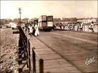 Abidjan, le pont de Treichville. – Cet ouvrage un peu primitif, un pont flottant, avait été édifié en 1931, approximativement à l'emplacement de l'actuel pont Houphouët Boigny, lequel a été construit en 1957. Franchissant la lagune Ebrié, il reliait les quartiers du Plateau et de Treichville. Ces quartiers sont issus du déguerpissement de villages Tchaman (le nom original des occupants des lieux, rebaptisés Ebrié par le colonisateur, en empruntant un terme péjoratif employé par la communauté abouré de Grand Bassam). Ainsi, le village de Dugbeyo, situé au sud du Plateau, est déplacé de l'autre côté de la lagune à Anoumabo,