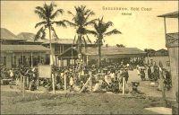 Seccondee, market. - La ville côtière de Seccondee (aussi orthographié Sekondi), dans l'Ouest de la Gold Coast, connait un important essor au tout début du XXème siècle. Elle bénéficie, après la guerre de 1900-1901 qui a permis de soumettre le pays ashanti, de gros investissements en infrastructures destinés à évacuer les richesses provenant des nouveaux territoires septentrionaux. Ainsi, une ligne de chemin de fer reliant Kumasi est déployée à partir de 1903 et un nouveau port est ouvert au trafic durant la décennie suivante. Ce dispositif permet d'acheminer le cacao, dont l'agriculture se développe, les bois tropicaux et les produits miniers et en particulier l'or dont l'extraction a bondit grâce aux investissements européens. La ville s'est développée autour du site d'un ancien fort hollandais du XVIIème siècle (une soixantaine de forts sont bâtis le long des 500 km de côtes de l'actuel Ghana à partir du XVème siècle par plusieurs puissances européennes). La ville voisine de Takoradi, sur le site d'un ancien fort anglais à quelques kilomètres à l'ouest de Sekondi, se développe à son tour dans les années suivant la première guerre mondiale. Elle est en effet choisie, par le gouverneur Gordon Guggisberg, pour recevoir le port en eau profonde qui portera le développement économique de la colonie. Les deux villes sont officiellement réunies en 1946, sous le nom de Sekondi-Takoradi.