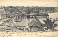 Beach and landing place at Sekondi, 1903, (la plage et la zone d'accostage de Sekondi en 1903). – La ville côtière de Sekondi, dans l'Ouest de la Gold Coast, connait un important essor au tout début du XXème siècle. Elle bénéficie, après la guerre de 1900-1901 qui a permis de soumettre le pays ashanti, de gros investissements en infrastructures destinés à évacuer les richesses provenant des nouveaux territoires septentrionaux. Ainsi, une ligne de chemin de fer reliant Kumasi est déployée à partir de 1903 et un nouveau port est ouvert au trafic durant la décennie suivante. Ce dispositif permet d'acheminer le cacao, dont l'agriculture se développe, les bois tropicaux et les produits miniers et en particulier l'or dont l'extraction a bondit grâce aux investissements européens. La ville s'est développée autour du site d'un ancien fort hollandais du XVIIème siècle (une soixantaine de forts sont bâtis le long des 500 km de côtes de l'actuel Ghana à partir du XVème siècle par plusieurs puissances européennes). La ville voisine de Takoradi, sur le site d'un ancien fort anglais à quelques kilomètres à l'ouest de Sekondi, se développe à son tour dans les années suivant la première guerre mondiale. Elle est en effet choisie, par le gouverneur Gordon Guggisberg, pour recevoir le port en eau profonde qui portera le développement économique de la colonie. Les deux villes sont officiellement réunies en 1946, sous le nom de Sekondi-Takoradi.
