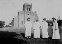 Eglise de Navrongo, au nord de la Gold Coast. – Visite, en 1929, de Mgr Joanny Thévenoud, vicaire apostolique de Ouagadougou, et du père Louis Durrieu,  reçus par le père Remigius McCoy et Mgr Oscar Morin. La mission dans les Territoires du nord de la Côte-d'Or a été fondée en 1906 à partir de la mission de Ouagadougou.
