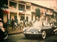 Le convoi du Général De Gaulle dans les rues de Conakry, le 25 août 1958 (cliché amateur de Léon Anselmo). – A la veille du référendum du 28 septembre 1958, le Général De Gaulle fait la tournée des capitales africaines. Il s'emploie à  convaincre les populations de voter en faveur de l'adhésion de leur territoire respectif à la Communauté française. Ce nouveau statut, qui confère aux colonies une grande autonomie, fait partie du projet de constitution de la Vème république. L'accueil du nouveau chef de l'exécutif français – il est revenu au pouvoir depuis quelques mois seulement, porté par les difficultés de la décolonisation algérienne – est contrasté. A Conakry, il est chaleureusement fêté, la population est mobilisée pour saluer son passage et Ahmed Sékou Touré est venu en personne le chercher à l'aéroport (on l'aperçoit d'ailleurs dans la voiture aux côtés du général) alors qu'à l'étape suivante de Dakar ni Léopold Sédar Senghor ni Mamadou Dia, le président du gouvernement du Sénégal, ne seront là. Mais bien vite c'est le malentendu : le discours du leader guinéen est une douche froide pour l'homme du 18 juin. Il clame préférer « la pauvreté dans la liberté, à la richesse dans l'esclavage » et appelle son peuple à refuser la Communauté pour choisir l'indépendance. Le Général De Gaulle est ulcéré, il prend acte sèchement en parlant de « sécession » et quitte Conakry très contrarié. Lors du référendum, le oui l'emporte largement dans toutes l'Afrique (y compris au Niger où l'administration a falsifié les résultats semble-t-il) sauf en Guinée qui accède à l'indépendance dès le 3 octobre. Et le torchon continue de bruler entre Conakry et Paris, puisque la passation de pouvoir prend la forme d'une rupture économique et politique brutale. Malgré les tentatives de réconciliations tentées par Sékou Touré, De Gaulle et Jacques Foccart - son homme de l'ombre en charge des affaires africaines – lui en tiendront rigueur jusqu'au bout, multipliant même les tentatives d'atten