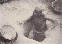 Siguiri, un mineur indigène chercheur d'or, entrant dans son trou. Cliché du ministère de la France d'outre-mer. - On extrait traditionnellement de l'or dans la région de la vallée du Haut-Niger, entre Kouroussa et Siguiri, depuis un millénaire ou plus. Les techniques de production fondées sur l'orpaillage, attestées dès le XVIIIème siècle dans l'empire du Mali dont cette région était le cœur, restent inchangées. Des puits individuels, traversant la cuirasse pour atteindre les alluvions aurifères, sont creusés et exploités en saison sèche. Le minerai, remonté dans des sceaux, est lavé à la batée par les femmes dans des calebasses. Les zones d'exploitation sont attribuées par les « maîtres de l'or », équivalents des « chefs de terre » dans l'agriculture. Commercialisée par les Dioulas, la majeure partie de la production alimente le marché intérieur, et notamment la bijouterie indigène, tandis qu'une fraction achetée par les sociétés de traite est exportée à partir du XXème siècle, entre 50 et 300 kilogrammes par an entre les années 1920 et 1930. Aujourd'hui encore, dans toute l'Afrique de l'Ouest et même au-delà, de très nombreux mineurs, opérant en marge des compagnies minières établies, ont recours à ces techniques d'exploitation archaïques. Elles occasionnent de fréquents accidents meurtriers.