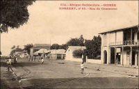 Konakry, rue du Commerce. – Connue également comme rue ou avenue commerciale, boulevard du Commerce ou encore « 3ème boulevard », cette artère majeure de la capitale guinéenne aboutit au port. L'administrateur Bie la décrit ainsi en 1899 : « n'a pas moins de 30 m. de large sur une longueur d'environ un kilomètre. De larges trottoirs bordant cette rue, de splendides maison à étage, toutes neuves, lui donnent une apparence toute moderne » (1). Le chemin de fer Decauville, que l'on distingue sur l'image, fut déployé dans ce quartier de négoce à partir de 1897. Cette installation, constituée de rails écartés de 60 cm et fixés sur des traverses métalliques, était souvent désignée comme « petite vitesse », par opposition au chemin de fer plus rapide et en voies métriques qui joignait le fleuve Niger. A partir de 1902, elle  totalisait 9,7 kilomètres de voies. Son usage n'était pas réservé au commerce, et les particuliers pouvaient y faire circuler des marchandises, moyennant un droit de 1 franc par tonne transportée et en fournissant le véhicule et son mode de traction. Les wagonnets de promenade, emportant des passagers, n'étaient pas soumis à cette taxe. Source (1) : Bie. A. (administrateur), Voyage à la côte occidentale d'Afrique, de Marseille à Conakry, Conakry le 20 mai 1899 (archive privée citée par Odile Goerg dans Rives Coloniales, Soulilou, Jacques, éditeur scientifique, Paris, édition Parenthèses et édition Orstom, 1993).