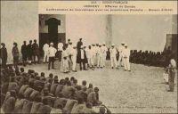 Conakry, affaire de Gomba, confrontation du Gouverneur avec les prisonniers Foulahs, maison d'arrêt. – La scène se situe en 1911. A cette époque, suite au retour en Guinée du roi du Labé Alpha Yaya Diallo – il avait était déporté au Dahomey en 1905 par le colonisateur -, des troubles politiques secouèrent le Foutah-Djallon. A la tête de cette insurrection, qui tentait de rétablir le pouvoir du souverain et l'indépendance de la région, se trouvent le Ouali de Gomba, Thierno Aliou, et Karamoko Sankoun de Touba. Pour mater la contestation, l'administration fit appel à la 7ème compagnie de tirailleurs sénégalais (en garnison à Kati près de Bamako), qui s'empara facilement de la localité de Touba. Mais, le 30 mars 1911, la troupe rencontra à Gomba une résistance sans précédent, qui devait coûter la vie au capitaine Talay qui la dirigeait, à un lieutenant et  à 12 tirailleurs. A force de combat Gomba tomba, la répression fut féroce et les captifs nombreux (comme le montre la photo). Thierno Aliou, qui avait fuit vers la Sierra Leone voisine, fut capturé et extradé par les Anglais, puis condamné à mort par la Cour d'Assise de Conakry. Octogénaire, le vieux chef mourut d'épuisement en détention avant même que son recours en grâce n'ait été rejeté. Alpha Yaya Diallo et ses proches furent exilés à Port Etienne, l'actuelle Nouadhibou. « L'année 1911 fut marquée par une très forte présence de détenus politiques parmi la population pénale », note l'historien Mamadou Dian Chérif Diallo (Répression et enfermement en Guinée. Le pénitencier de Fotoba et la prison de Conakry de 1900 à 1958, Paris, L'Harmattan, 2005). En Guinée, les régimes changent, mais la violence répressive reste une constante de l'arsenal politique...