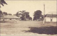 Conakry, Hôtel du Port et avenue de la Gare, petite vitesse. – La « petite vitesse » désigne le chemin de fer Decauville, dont on voit ici les rails au milieu des rues, qui sillonnait la ville de Conakry, comme celles de beaucoup d'autres capitales coloniales africaines. Les voies Decauville étaient constituées de rails écartés de 60 cm, fixés sur des traverses métalliques. – « Philippe, s'exclama tout à coup Andrée, je ne comprends rien à votre Decauville. Tout à l'heure, j'y voyais passer un train minuscule, puis ce fut un camion chargé de pierres et traîné, à bras, par des Noirs. Maintenant, regardez cette voiture élégante où trône une jeune femme, à demi cachée sous son ombrelle, tandis que son compagnon conduit le cheval. – Notre Decauville, expliqua Dorhez en souriant, n'est pas, comme en France, un égoïste, gardant les rails pour lui tout seul. Ici, ce chemin de fer sur route est mis à la disposition du commerce et même des particuliers, moyennant un droit fixé à un franc par tonne. Chacun fournit son véhicule et son moyen de traction. – Comme à Rufisque, remarqua l'Oncle Guy. – Un franc la tonne, reprit Andrée, alors cette jeune dame... -- ... n'a pas besoin de se peser, rassurez-vous, répliqua Dorthez. Ici les wagonnets de promenade ne payent aucune taxe ». Source : Decourt, Dr Ferdinand, La famille Kerdalec au Soudan, Paris, Ed. Librairie Vuibert, 1910.
