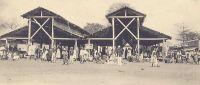 Kindia, le marché vers 1900. – Chef-lieu du cercle du même nom, la ville de Kindia est caractérisée par « une grande rue principale allant de la Résidence [du commandant de cercle] à la gare [ligne Conakry-Kankan], en passant par la place du marché… […] La population, en dehors de l'élément fonctionnaire et militaire, comprend essentiellement les planteurs et les commerçants. » source Guid'AOF, Dakar, 1948.