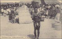 Bobo-Dioulasso, le marché. –En mars 1890, le commandant Monteil fait étape à Bobo-Dioulasso, durant sa fameuse expédition de Saint-Louis du Sénégal à Tripoli en passant par le Lac Tchad. Il décrit le marché et ses échanges en ces termes : « Bobo-Dioulasso est un marché important où se tissent des cotonnades célèbres d'une grande finesse de trame en même temps que de grande solidité. Les principales transactions du marché portent sur l'or, la noix de kola et le coton. La noix de kola vient du sud du Ouorodougou et de Gondia ». Pour l'explorateur, le séjour dans cette ville voltaïque réserve quelques déconvenues. Il y est abandonné par la fuite de ses porteurs. Outre ces derniers, il voyage avec une troupe légère, composée d'un adjudant français et de douze tirailleurs sénégalais. Il soupçonne son cuisinier d'être l'organisateur de cette défection. Mais celui disparait à son tour, avant de reparaitre à Ségou, où il raconte une histoire confuse aux autorités militaires françaises, évoquant le massacre par des brigands de toute la mission Monteil, dont il serait le seul survivant. Mais son affabulation ne convainc pas et il est décapité pour désertion. Monteil, qui relate cet épisode, prit connaissance de son issue après son retour en France. Réputé esprit audacieux – il prédit même l'indépendance de l'Indochine dans ses écrits dès le début du XXème siècle -, il ne parait pourtant pas choqué ou même affecté par la sévérité de la sanction pour une faute si vénielle… Cette photographie, localisée au Haut-Sénégal-Niger, se situe chronologiquement entre 1904, création de ce territoire, et 1919, naissance de la colonie de Haute-Volta.