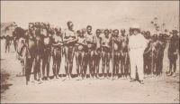 Chez les Lobis, le coin des « Yona », femmes. – La rencontre avec la nudité – partielle ou totale - de certains groupes africains surprend les occidentaux de la fin du XIXème et du début du XXème siècle. Particulièrement celle des femmes, qui n'est pas coutumière dans l'Europe d'alors. Les témoignages sur le sujet, écrits ou photographiques, sont nombreux. Ils mettent parfois en scène, comme ici, une représentation étrange à force de contrastes, où le colonisateur se montre très habillé aux côtés d'Africains dévêtus. Ce genre de tableau semble à la fois flatter le gout de l'exotisme des visiteurs et justifier implicitement l'ambition civilisatrice –au sens normatif- de l'action coloniale… L'écrivain Jacques Soubrier, auteur de romans pour les jeunes et de récits voyages, raconte ainsi sa rencontre avec les tribus Lobis les jours de marché à Gaoua lors d'un périple africain : « Les femmes n'ont pour tout costume que la ceinture de ficelles, en brin de « bemwos », dont les extrémités leur pendent jusqu'aux genoux. Les femmes mariées portent, en outre, comme chez les Bobos, deux bouquets de feuilles, qu'elles s'appliquent avec beaucoup de pudeur lorsqu'elles se baissent. La plupart ont les lèvres déformées par l'affreux labret de quartz, de fer, d'os ou de bois, et des scarifications en étoile leur ornent le nombril. Leurs traits sont en général assez fins et l'habitude, commune à toutes les femmes noires, de porter les fardeaux sur la tête donne à leur démarche et à leur port l'élégance et la noblesse que l'on remarque, pour la même raison, chez nos Arlésiennes » (1). Carte postale signée « Cliché Mission d'Art Colonial ». Source : Soubrier, Jacques, Savanes et Forêts, Paris, J. Susse, 1944.