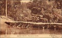 Pont sur la Leraba. Affluent du fleuve Comoé,  cette rivière délimite par endroit la frontière entre la Haute-Volta et la Côte d'Ivoire. Elle doit être franchie pour aller d'Ouangolodougou à Niangoloko, sur la route qui permet de gagner la Haute-Volta depuis la Côte d'Ivoire. Ce pont sommaire était donc un passage obligé pour les voyageurs se rendant ou venant au port d'Abidjan, la fenêtre maritime de la colonie voltaïque. Faute de voies navigables suffisantes (les cours d'eau n'étaient utilisés que sur des tronçons et de manières saisonnières) et en attendant l'arrivée tardive du chemin de fer (la ligne d'Abidjan ne devait atteindre Bobo-Dioulasso qu'en 1932 et Ouagadougou en 1954), les infrastructures routières ont été développées assez tôt en Haute-Volta. - « Privée de débouchés naturels et de voies ferrées, la Haute-Volta est, par contre, sillonnée d'admirables routes. Beaucoup d'autos la parcourent. Elles assurent la vie du pays. Le gouvernement en a, pour son compte, une soixantaine, postales et autres ; c'est un véritable parc d'armée. Les autos, et non le chemin de fer, ici comme ailleurs, sont l'avenir » (1). Sources : (1) Morand, Paul, A.O.F. de Paris à Tombouctou, Paris, Flammarion, 1928.
