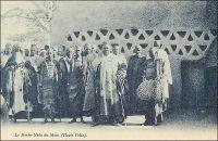 Le Morko-Naba du Mossi. – « Hier, à Ouagadougou, j'ai été rendre visite au Moro-Naba, le roi de tout le pays Mossi. Il règne sur deux à trois millions de sujets et ses ancêtres furent en rapport avec les Portugais. M. Delafosse a même pu établir la chronologie des rois Mossi jusqu'à l'an mil. Le roi m'attend sur la porte de son palais, entouré de sa cour. Il est obèse ; une vraie outre noire, grasse ; l'air sensuel, féroce et malin. Barbiche, joues énormes. C'est bien le dernier roi nègre, celui de mes livres d'enfant. Il porte une énorme couronne d'or, une robe de velours violet soutachée d'or, et rafraîchit ses lourdes lèvres violacées d'une petite langue de carmin qui égaye de sa couleur tout le visage. Il me présente ses ministres, ses scribes, ses eunuques, ses pages, très beaux et vêtus de robes, coiffés en cimier, comme des femmes, comme elles guêtrés de jambières de cuivre de vingt centimètres de haut, parés de lourds anneaux de cuivre rose, d'une tonalité merveilleuse sur la peau nue. […] J'offre au Moro-Naba un bracelet d'émeraudes, acheté à Paris dans une de ces boutiques de faux à « tout pour cent francs… » (1). - Il doit s'agir du Mogho Naaba Koom II (1889 – 1942), l'arrière grand-père du Mogho Naaba actuel, qui régna du 27 février 1905 à sa mort, le 12 mars 1942. Il avait choisi pour devise « Que l'eau abonde pour tous ». Il repose, ainsi que sa femme, au centre de la place qui porte son nom devant la gare ferroviaire de Ouagadougou, sous la masse d'une statue métallique de 6 mètres de haut représentant une femme mossi stylisée offrant l'eau de bienvenue à un hôte invisible. Mogho Naaba Koom II s'était rallié à la France Libre dès le 22 juin 1940, alors que Paul Morand, dont on sent percer le dédain dans les lignes que lui a consacrées, sera nommé ambassadeur de France en Roumanie puis en Suisse par Vichy. Source : (1) Morand, Paul, A.O.F. de Paris à Tombouctou, Paris, Flammarion, 1928.