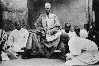 Naba (chef) de Canton entouré de ses pages. – « Avant le déjeuner, à Ouaygouya, où nous fîrmes étape, je suis allé voir le Naba ; c'est le roi du pays Mossinord ; ce Naba est en rivalité avec son confrère du sud, le Moro-Naba, roi de Ouagadougou. Sans nous, ces tyranneaux auraient vidé depuis longtemps leur querelle par les armes. Celui-ci ne parle pas français ; il est magnifique ; vrai Sarrasin de légende, haut de deux mètres, drapé dans une belle robe de soie blanche, tout enturbanné de blanc, portant avec une agressive dignité un ventre énorme, une dizaine de gros sachets magiques rouges pendus autour du cou. On le dit riche et il reçoit très poliment mes dons, avec un parfait mépris. [...] Ce Naba me fait penser aux anciens rois nègres, aux roitelets du Sénégal du XVIIè ou du XVIIIè siècle. N'est-il pas pareil à ce « petit Brac » que décrit ainsi Labat : « Tout l'habit et le baudrier étaient parsemés de gris-gris enveloppés fort proprement dans du drap écarlate, du maroquin rouge ou des peaux de bêtes sauvages. » (1). Paul Morand, qui raconte sa rencontre avec les autorités traditionnelles de Haute-Volta à l'occasion d'un périple à travers l'AOF à la fin des années 1920, se méprend sur le rôle stabilisateur de la France au Mossi. Contrairement à ce qu'il croit, les royaumes du Mossi ont une organisation politique pérenne. C'est à elle qu'on attribue le fait qu'ils aient résisté à toutes les incursions, y compris à la conquête islamique, depuis leur formation au XIIè siècle et jusqu'au début des avancées occidentales au XVIIIè siècle. Ils ont ainsi échappé à la traite négrière, et constituent de ce fait, un formidable réservoir de main d'œuvre auquel le colonisateur fera systématiquement appel. Par ailleurs, Paul Morand convoque un peu hâtivement Jean-Baptiste Labat, l'auteur de Nouvelle relation de l'Afrique occidentale, pour sa description des roitelets du Sénégal. On sait – et cela avait déjà été publié lorsque Morand a écrit ces lignes – que l'ecclésiastique