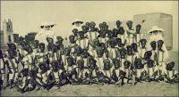 Ouagadougou, groupe de petits élèves de la classe de français. – « La première caravane de Sœurs Blanche arrivait au Mossi, le 3 décembre 1912. [...] Ainsi fut fondée, en 1921, l'école cléricale. [...] Presque tous ses élèves sont des enfants de chrétiens de Ouagadougou (quelques exceptions sont faites pour des enfants de païens). Cependant les succursales et les postes avoisinants envoient aussi leurs garçonnets. [...] Ces enfants nous arrivent vers 6, 7 et 8 ans ; en principe, ils font 5 années de primaire ; en pratique c'est six ans pour beaucoup. Notre école est donc partagée en cinq cours. Une Sœur est chargée de la direction de l'école ; une autre de la première classe. [...] Débutant jeunes à l'école, doués d'une bonne mémoire, nos enfants apprennent vite à lire et leur prononciation est bonne, sauf pour certains sons : S et Ch, E et è, J et Z que les indigènes confondent facilement. [...] Quand ils nous arrivent, ce sont de petits sauvageons au regard apeuré, au geste craintif. Ils connaissent les Pères mais non la Sœur. Pendant quelques jours, ils salueront d'un gentil « Bonjour, mon père ». L'un deux imagina cette définition : « Une Soeur, c'est un père sans barbe ». » Source : Thevenoud, Mgr Joanny, Dans la boucle du Niger, Namur, éditions Grands Lacs, 1938.
