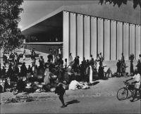 Ouagadougou, le marché, vers 1950. – Il s'agit du marché central Rood Woko, peu après sa construction. Le nom Rood Woko est composé de deux mots qui signifient respectivement en mooré « fréquenter » et « long », lesquels, mis ensemble, évoquent un marché animé quotidiennement, par opposition à d'autres qui sont périodiques. Agrandi et modernisé en 1983, ce marché a été partiellement détruit dans un incendie le 27 mai 2003, et fermé. Officiellement, le sinistre est imputé à un court-circuit, mais le marché se situe dans une zone qui était alors en cours de démolition, dans le cadre de l'opération « Zaka » destinée à créer un centre ville « moderne » après avoir déplacé les anciens occupants vers la grande périphérie de la capitale… Après des années atermoiements, d'annonces contradictoires, et de tensions parfois violentes entre autorités municipales et commerçants, les travaux de réhabilitation de l'édifice ont débuté le 27 août 2007, 51 mois jour pour jour après l'incendie.