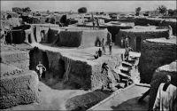 Quartier indigène de Bobo-Dioulasso. – Il s'agit d'un cliché de l'Agence économique des colonies qui situe la scène en Côte d'Ivoire. Cela signifie que la scène se situe dans l'intervalle entre 1932 et 1947, durant lequel la colonie de Haute-Volta a été intégrée aux colonies adjacentes. « Bobo-Dioulasso est une des ville les plus importante de la Côte d'Ivoire et forme la tête de ligne actuelle du chemin de fer qui remontera plus tard jusqu'à Ouagadougou… » (1). « Bobo est un gros centre cosmopolite : plus de 10 000 indigènes de toutes races s'y sont donné rendez-vous (Malinké, Bambara, Dioula, Mossi, Sia et Bobo). La gare domine la cité où émergent de-ci de-là quelques minarets. En sortant, nous voyons d'immenses entrepôts qui témoignent de l'activité commerciale de cette cité ; puis de larges avenues descendent en patte d'oie vers le centre de la ville, celle de droite nous conduit à la place de l'Etoile, à quelques mètre de laquelle nous apercevons les bâtiments de la mission des Pères Blancs » (2). « A Bobodioulasso, où nous couchons, nous trouvons la vraie capitale économique de la Haute-Volta. La ville est riche et se développe » (3). Sources : (1) Soubrier, J., Savanes et forêts, éditions J. Susse, Paris, 1944. (2) Paternot, Marcel, Lumière sur la Volta – Chez les Dagari, Lyon, Editions de la plus grande France, 1946. (3) Morand, Paul, A.O.F. de Paris à Tombouctou, Paris, Flammarion, 1928.