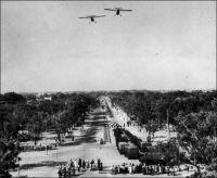 Ouagadougou fête l'indépendance de la Haute-Volta, au début des années 1960 (photo publiée courant 1963). – La colonie de Haute-Volta, créée en 1919, puis supprimée et intégrée aux colonies françaises mitoyennes entre 1932 et 1947, devient une république au sein de la Communauté française le 11 décembre 1958. La Haute-Volta accède à l'indépendance le 5 août 1960. Pourtant, le Burkina Faso a récemment pris le parti de célébrer son indépendance le 11 décembre. Ce transfert de date anniversaire n'est pas fortuit. D'une part la date du 5 août était trop proche dans le calendrier de celle du 4 août, anniversaire de la prise du pouvoir par le populaire capitaine Thomas Sankara en 1983, lequel sera liquidé quatre ans plus tard par des hommes à la solde de l'actuel président Compaoré. D'autre part, pour la majorité de la population, qui n'a pas connu l'époque coloniale, la première quinzaine de décembre correspond à la commémoration de l'assassinat du journaliste Norbert Zongo, le 13 décembre 1998. L'homme de presse, qui s'acharnait à traquer les crimes et turpitudes du pouvoir, accusait notamment le frère du président Compaoré d'avoir fait assassiner son chauffeur pour une obscure histoire de vol. Le journaliste a été exécuté, avec ses compagnons de voyage, près de la localité de Sapouy, sur une piste bordée de caïcédrats qui va de Léo à Ouagadougou. L'événement avait soulevé une violente émotion populaire, qui se ranime chaque année au moment de l'anniversaire de la tragédie. Des enquêtes indépendantes ont établi la responsabilité de membres de la garde présidentielle dans cet attentat, sans pourtant qu'aucun n'ait été condamné par la justice burkinabè. Le changement de date de la fête d'indépendance permet de libérer salariés, élèves et étudiants pour une semaine fériée, amenuisant le risque d'une émulation qui générait jusqu'alors des émeutes chaque année. - Les appareils qui évoluent en formation semblent être les deux Broussards (Max Holste MH 1521), dont l'ancien col