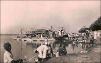 Fort-Lamy, l'arrivée du bac de Koussery. – « Lorsqu'on arrive à Fort-Lamy par le fleuve, on voit une ligne d'arbres vert sombre, dominés du drapeau français, ponctuée de flamboyants et cachant des maisons blanches. A cet endroit la rive du fleuve, aux basses eaux, est élevée comme une falaise. On croit à un paradis de verdure à l'abri des eaux. Avant ce promontoire de feuilles, la rive s'est abaissée en pente douce et sableuse ; les pirogues chargées de poissons, de bois, de paille, d'hommes, de femmes, d'enfants, d'animaux, de calebasses ; ouvertes de frêles, lourdes et couvertes de shimbecks de paille, grées de filets immenses et des apparaux de la pêche, ou nues ; de baleinières de métal, poussées par des perches ; un bac transportant un camion, c'est le port. » Source : Lapie, Pierre Olivier, Mes tournées au Tchad, Londres, John Murray, 1941.