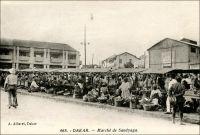 Dakar, le marché Sandyaga. - Construit entre 1933 et 1935, le marché Sandaga quelques fois orthographié « Sandyaga » comme ici ou « Sandiaga » - tiendrait son nom d'un arbre, « dang ga », marquant à l'époque son centre. Ce marché répond à une logique d'organisation ségréguée de la ville coloniale, progressivement instaurée dans la capitale sénégalaise depuis sa création dans la seconde moitié du XIXème siècle. Comme le note la légende manuscrite de l'auteur de cette photo, il est dévolu aux échanges des indigènes, et est situé le long d'axes menant aux quartiers périphériques où ils sont relégués. Sandaga approvisionne des marchés secondaires, formels et informels, situés dans les faubourgs populaires de la Médina. Les Européens, qui habitent dans le quartier du Plateau -agréablement tempéré par le vent du large-, vont au marché Kermel. Dans les rues autour de Sandaga se développe rapidement une zone commerciale très dynamique. Elle était tenue, jusque récemment, par de si nombreux marchands libanais qu'on désignait parfois Dakar sous le nom de « Beyrouth 2 ». Ils semblent avoir cédé la place à des commerçants sénégalais appartenant à la confrérie mouride. Sources : Sinou, Alain, Rives Coloniales, Paris, éditions Parenthèses et éditions de l'Orstom, 1993.