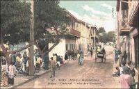 Dakar, rue des Essarts. – Cette artère, qui conserve de nos jours son tracé initial, est l'une des plus anciennes de la capitale sénégalaise. Son nom, qui n'a jamais changé,  fait vraisemblablement référence au défrichage nécessaire à son édification. Elle fut dessinée ex nihilo en 1862 - cinq ans seulement après l'installation française sur la presqu'île du Cap Vert - par le capitaine du génie Pinet-Laprade. Celui-ci organisa le premier plan d'urbanisme de la ville, en s'inspirant du modèle d'une petite bourgade de province : il jette ainsi un boulevard portant son nom, quelques rues perpendiculaires et parallèles, dont la rue des Essarts, et une place centrale accueillant les activités de commerce, la place Kermel et le marché du même nom. Haut-lieu du quartier historique, la rue des Essarts accueillera, au fil du temps, le siège, la succursale locale ou la représentation pour l'AOF – dont Dakar était la capitale depuis 1902 -  de nombreux opérateurs économiques et commerciaux, comme le Crédit Lyonnais, les magasins de confection « Ghislaine » et « Jaoudi », la CITEC – fournisseur officiel de « La toile d'avion » -, la Société anonyme de ravitaillement maritime… - Cette carte postale fait partie de l'importante collection due au photographe et éditeur dakarois Edmond Fortier (1862-1928), qui tenait d'ailleurs boutique rue Dagorne, une des voies transversales coupant la rue des Essarts au niveau du marché Kermel.