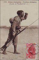 Tirailleur sénégalais. - 212 000 Africains de toute l'AOF, prirent part en tant que tirailleurs sénégalais aux hostilités de la Grande guerre, dont 165 000 sur le sol métropolitain. 30 000 furent tués. Le corps des tirailleurs sénégalais avait été créé en 1857 par Louis Faidherbe, alors gouverneur général de l'AOF, pour palier, en cette époque de conquête coloniale, le déficit de troupes venant de Métropole. Initialement composés d'esclaves rachetés à leurs maîtres africains et affranchis et de volontaires issus des élites locales, les régiments de tirailleurs sénégalais s'apparentent à des troupes mercenaires. Mais la mobilisation de tous les Africains de plus de 18 ans décidée en 1915, et leur engagement pour défendre la Nation, vont en faire un corps d'engagés et de conscrits des plus légitimes. 17 régiments de tirailleurs sénégalais participent à la bataille de la Somme, subissant d'importantes pertes qui vaudront au Général Mangin, par ailleurs promoteur des troupes africaines, le surnom de « boucher des noirs ». - Cette remarquable photo, publiée en carte postale,  fait partie du travail du célèbre photographe et éditeur dakarois Edmond Fortier (1862-1928). On lui doit une somme importante de clichés sur l'Afrique de l'Ouest en général et sur le Sénégal en particulier ; il a publié en tout 3300 clichés originaux. M. Fortier tenait boutique et vivait avec ses deux filles blondes et son boy Seydou Traoré, à l'angle de la rue Dagorne et du boulevard Pinet-Laprade, tout près du marché Kermel.