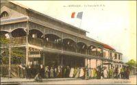 Rufisque, la gare du DSL. - Les travaux de construction de la ligne de chemin de fer entre Dakar et Saint-Louis (DSL) commencent simultanément à partir de Rufisque et de Saint Louis en 1883, et le tronçon de 28 km entre Rufisque et Dakar est le premier à entrer en exploitation dès juillet 1883. La gare de Rufisque connaît un essor avec l'ouverture de la ligne vers Djourbel au début du XXème siècle. Cet embryon de la ligne Thiès-Kayes draine en effet un important trafic lié à l'arachide. Ainsi, en 1909, 45 000 t. d'arachide sont débarquées à la gare de Rufisque. Cette ville, qui s'est développée progressivement à partir du XIVème siècle sur un site initialement occupé par des villages de pécheurs, est alors le principal centre de traitement et d'exportation de l'arachide. Rufisque s'est imposée dans cette activité au cours du XIXème , grâce à sa situation géographique, à la porte du Cayor, et à son port. En 1880, 23 000 tonnes d'arachides sont exportées depuis Rufisque, soit plus de la moitié des exportations de la colonie. Centre commercial et administratif important, Rufisque devient une commune avant même Dakar, le 12 juin 1880. Mais elle connaît dès la fin des années 1920 un déclin inexorable. Ses activités portuaires sont concurrencées par celles d'autres villes, Dakar et Kaolack notamment. Son rayonnement a pali depuis que Dakar est devenu en 1902 la capitale de l'AOF et reçoit la majeure partie des investissements publics. L'âge d'or de Rufisque s'achève définitivement avec la crise économique des années 1930. La gare de Rufisque est classée parmi les monuments historiques du Sénégal depuis les années 1970.