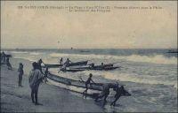 Saint-Louis, la plage à Guet N'Dar, premiers départs pour la pêche, le lancement des pirogues. – Les habitants de Guet N'Dar, le quartier de Saint-Louis situé entre le petit bras du fleuve Sénégal et l'océan, sont réputés pour leurs qualités de pêcheurs et de navigateurs. A l'époque coloniale, la pêche, activité artisanale et spécifiquement indigène, était peu considérée par les acteurs économiques établis. Ainsi, elle n'était pas prise en compte par les Chambres de commerce, d'agriculture et d'industrie de Dakar et de Saint-Louis, qui géraient pourtant les activités maritimes de la colonie - notamment en exploitant les ports fluvio-maritimes grâce à une flottille de remorqueurs et chalands. Depuis cette époque, la pêche piroguière sénégalaise a connu une forte expansion. Au cours des cinquante dernières années, le nombre d'embarcations traditionnelles a été multiplié par cinq, et les prises de poisson continuent encore actuellement de croître, atteignant 361 000 tonnes en 2007. Directement ou indirectement, le secteur emploie 15 % de la population active du Sénégal. Les pêcheurs de Saint-Louis louent quelques fois leurs services à en capturant du poisson pour des flottes étrangères stationnées au large. Contrairement à une idée souvent véhiculée par la presse occidentale et sénégalaise, les pêcheurs sénégalais ne sont que très marginalement impliqués dans l'émigration irrégulière et périlleuse vers les îles Canaries, avant poste des frontières européennes (1) – Le photographe Pierre Tacher (1875-1938), qui signe ce cliché, fut l'éditeur de cartes postales le plus prolixe de Saint-Louis au début du Xxème siècle. Il repose au cimetière de Sor, un quartier de Saint-Louis, aux côtés de son fils que l'on peut voir sur une autre image du site. Sources (1) Sall, Aliou et Morand, Pierre.