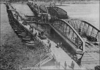 Saint-Louis, pendant la construction du Pont Faidherbe. – Pendant la construit du pont métallique Faidherbe, inauguré en 1897, le pont de bateaux inauguré en 1865, et qui s'appelait déjà pont Faidherbe, reste en service. La traversée du grand bras du fleuve Sénégal, entre le quartier continental de Sor et l'île de Saint-Louis, était assurée depuis 1865 par un bac. Le nouveau pont Faidherbe, possède, comme le pont de bateaux avant lui, un point de passage pour les navires. En l'occurrence, la deuxième travée, à partir de la rive saint-louisiènne est mobile autour d'un pivot situé sur une pile. Le pont fait 511 mètres de longs, pour 10,50 mètres de large, avec une chaussée de 7 mètres et deux trottoirs piétons de 1,60 mètres. Ce projet avait été choisi pour son esthétique ; elle ne fut pas altérée par la restauration intervenue en 1931.