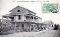 Louga, la gare. – « Louga (Sénégal) février 1885. […] N'ayant rien trouvé dans le commerce, j'entrai à la Compagnie du chemin de fer de Dakar à St-Louis, dont la construction s'achève. On m'envoya ici [à Louga], quatrième station depuis St-Louis, je ne savais rien, ni de la compagnie, ni des règlements ni du télégraphe. Je me suis acharné sur le « Bréguet » et je puis tout de même recevoir et passer une dépêche, pourvu que mes voisins n'aillent pas trop vite. La gare est une construction en bois et briques : un bureau, une chambre à coucher, une salle à manger et une cuisine. J'ai des appointements superbes : 200 francs par mois. […] Près de la gare, un village s'est créé depuis peu : de simples cases de paille, habitées par des commerçants indigènes, des traitants comme on les appelle, car le commerce des arachides se nomme la traite. La plupart de ces traitants sont convenables, et l'un d'eux, nommé Cambel, Ouolof de St-Louis, discret et bien élevé, vient souvent causer avec moi. […] Les voyageurs européens profitent de l'arrêt du train pour venir se rafraîchir ; ils savent qu'il y a dans la salle à manger une gargoulette pleine d'eau fraîche, avec un peu d'absinthe. Le train venant de St-Louis passe à 9 heures du matin et revient à 3 heures du soir ». Source : Correspondance d'Albert Nebout (1862-1940), rassemblée et publiée dans Nebout, Albert, Passions Africaines, Genève, Editions Eboris, 1995. - Cette carte postale fait partie du travail du célèbre photographe et éditeur dakarois Edmond Fortier (1862-1928) à qui l'on doit une somme importante de clichés sur l'Afrique de l'Ouest en général et sur le Sénégal en particulier ; il a publié en tout 3300 clichés originaux. M. Fortier tenait boutique et vivait avec ses deux filles blondes et son boy Seydou Traoré, à l'angle de la rue Dagorne et du boulevard Pinet-Laprade. – Quoique contemporains, ils sont nés tous deux en 1862, Albert Nebout et Edmond Fortier ne se sont vraisemblablement jamais rencontrés, le premier 