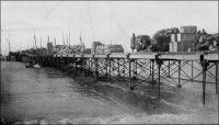 Le wharf de Rufisque pendant la traite des arachides. – La ville de Rufisque, qui s'est développée progressivement à partir du XIVème  siècle sur un site initialement occupé par des villages de pécheurs, devient au cours du XIXème siècle le principal centre de traitement et d'exportation de l'arachide. Elle s'est imposée dans cette activité, grâce à son port et à sa situation géographique, à la porte du Cayor. En 1880, 23 000 tonnes d'arachides sont exportées depuis Rufisque, soit plus de la moitié des exportations de la colonie, et en 1909, 45 000 tonnes. Centre commercial et administratif important, Rufisque devient une commune avant même Dakar, le 12 juin 1880. Mais elle connaît dès la fin des années 1920 un déclin inexorable. Ses activités portuaires sont concurrencées par celles d'autres villes, Dakar et Kaolack notamment. Son rayonnement a pali depuis que Dakar est devenue en 1902 la capitale de l'AOF et reçoit la majeure partie des investissements publics. L'âge d'or de Rufisque s'achève définitivement avec la crise économique des années 1930. A visiter : http://www.rufisquenews.com/rufisque_une_ville_une_histoire.html