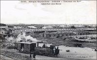 Dakar, travaux du port, chantier des blocs. – La ville de Dakar, devenue en 1902 la capitale de l'AOF, reçoit dès lors de forts investissements publics, pour développer les infrastructures tant civiles que militaires. Progressivement, le port qui est desservi par le chemin de fer à partir de1883, s'impose devant les autres installations du pays, et notamment Rufisque et Saint Louis. La machine à la manœuvre est la locomotive n°2 de type 030 T, fabriquée par les ateliers des Batignolles à Paris en 1883. – Cette photo fait partie du travail du célèbre photographe et éditeur dakarois Edmond Fortier (1862-1928) à qui l'on doit une somme importante de clichés sur l'Afrique de l'Ouest en général et sur le Sénégal en particulier ; il a publié en tout 3300 clichés originaux. M. Fortier tenait boutique et vivait avec ses deux filles blondes et son boy Seydou Traoré, à l'angle de la rue Dagorne et du boulevard Pinet-Laprade.