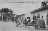 Thiès, une rue. - Thiès est le chef lieu du cercle du même nom, lequel compte, en 1948, une population de 2797 Européens et 272 692 Africains, dont 144 330 Ouoloffs, 91 754 Sérères et 12 369 Peuhls, pour une densité de 40,5 hab/km². La ville elle-même compte 24 783 Africains, 1350 Européens et 624 étrangers. Par comparaison, le recensement mené pour la ville de Dakar au début de cette même année 1948, dénombre 192 567 habitants, dont 167 055 non européens (troupes comprises), 16 112 Français, 500 étrangers (non compris les Libano-Syriens), 400 Français métis, 4500 Libano-Syriens et 4000 ressortissants étrangers non européens (principalement Portugais). Source : Guid'AOF, édition 1948. - Cette photo fait partie du travail du célèbre photographe et éditeur dakarois Edmond Fortier (1862-1928) à qui l'on doit une somme importante de clichés sur l'Afrique de l'Ouest en général et sur le Sénégal en particulier ; il a publié en tout 3300 clichés originaux. M. Fortier tenait boutique et vivait avec ses deux filles blondes et son boy Seydou Traoré, à l'angle de la rue Dagorne et du boulevard Pinet-Laprade.