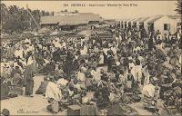 Saint-Louis, marché de Guet N'Dar. – « Enfin, quatorze jours après notre départ de Cadix, la Sarah abordait la côte sénégalaise et, après avoir contourné la pointe de Barbarie, dépassé l'île aux Gazelles, jetait l'ancre devant Guett N'Dar, à deux milles environ de Saint-Louis, capitale des établissements français, dont nous étions séparés que par une langue de sable au-delà de laquelle coulait le fleuve Sénégal parallèlement à la mer. […] Le troisième jour de notre arrivée, nous fîmes une excursion aux étangs salins de Gandioles situés près de l'embouchure même du Sénégal. […] Nous assistâmes aussi à une pêche faite à notre intention par les gens de Guett N'Dar, qui approvisionne le marché de Saint-Louis, qui se tient dans leur village ». (1) « Les diguenns, il a fallut les laisser là bas, à Saint-Louis, dans le faubourg de Guet N'Dar ; et ici pas moyen de les remplacer ; les sauvages des lagunes, ces Kroomen musclés et découplés, gardent les leurs jalousement ; et les femelles Bakoué ou Neyo, qui viennent de la forêt apporter la gomme et la poudre d'or sont tellement frustres, tellement sales et peu appétissantes avec leur grande cicatrice frontales, leurs dents aiguisées en pointe et les lobes outrageusement distendus de leurs oreilles, qu'un fils de Sénégal ne peut décemment, y consentirait-elle, mener dans son case une de ces ménagères là ; alors, il faut se passer d'amour, habiter le gourbi commun, et vaquer soi-même aux basses besognes ; Ô déchéance ! » (2). Il est à noter que l'orthographe du nom de ce quartier de Saint-Louis varie encore entre la fin du XIX ème, quand Jacolliot décrit son escale, et le début du XX ème siècle, lorsque Fortier légende sa photo et, plus tard, que D'Alem fait parler des tirailleurs dans son roman. Sources : (1) Jacolliot, Louis, Voyage aux rives du Niger, Paris, C. Marpon et E. Flammarion, 1879. (2) D'Alem, Gilbert, Madame Samory – roman soudanais, Paris, Plon, 1924.