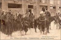 Tombouctou, groupe de Touareg. « Tombouctou s'éveille. Et pendant que les marabouts, devant le soleil levant, rappellent au peuple prosterné la grandeur d'Allah, sur le fort Bonnier monte le drapeau de la France. A ce moment, une compagnie de tirailleurs et deux pelotons de spahis sortent de la ville […] Combien reviendront de ceux qui partent ainsi à la recherche du rezzou de Touaregs signalé dans l'Est, au bord du Niger ? Les Touaregs ! guerriers légendaires, invisibles et toujours présents, survenant au galop de leurs chevaux ou de leurs méharas, tels une trombe de sable soulevée par le vent, ouragan qui passe, renverse tout et s'évanouit à l'horizon en fumée. Les Touaregs ! hommes voilés du désert, dont le litham (voile noir qui couvre le visage des Touaregs et ne laisse voir que les yeux et le nez) ajoute un mystère à celui de leur retraite » (1). Ce cliché, pris par le photographe et éditeur dakarois Edmond Fortier (1862-1928) doit dater de 1905, époque à laquelle il se rendit au Soudan et ne put, comme tous les voyageurs européens, couper à la visite de cette ville mythique aux portes du désert. Le journaliste Albert Londres, qui fit un périple en Afrique de l'Ouest en 1928 et s'y rendit à cette occasion, note pour sa part que les Européens de la colonie déconsidèrent ostensiblement cette étape ultime au nord de l'Afrique subsaharienne. « Un pèlerin qui monte à Tombouctou perd de sa valeur, à leurs yeux. Il passe pour un poète » (2).  Sources : (1) Baratier, Col., A travers l'Afrique, Paris, Arthème Fayard, 1908. (2) Londres, Albert, Terre d'ébène, Paris, Albin Michel, 1929.