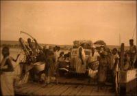 Descente du bac à Bamako, photo d'amateur. - La capitale du Soudan, quoique érigée au bord du fleuve Niger, ne reçoit son premier pont qu'en 1947 -le second est bâti durant le funeste régime du président Moussa Traoré (1968-1991) et le troisième, financé par la Chine, es en cours d'édification depuis 2009. Le bac sur le fleuve resta fonctionner bien après la mise en service du premier édifice. Le journal local L'Essor, dans sa livraison du 8 février 1960, révèle les statistiques de passages du bac entre le 18 juillet et le 1er décembre 1959. Dans cette période, 320 000 passagers, 15 000 vélos, 2000 charrettes, 5000 voitures, 1500 camionnettes, 5000 camions, dont 3000 véhicules lourds et légers  appartenant à l'administration, l'armée, la gendarmerie ou la police ont emprunté le bac, à raison de 145 véhicules et 2400 voyageurs par jour.