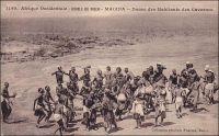 Macina, danse des habitants des cavernes. – Il s'agit vraisemblablement de Macina en tant que région, correspondant au royaume peul du XIX ème siècle, qui s'étendait de Tombouctou à Mopti et du Mossi à la Mauritanie. Quant aux habitants des cavernes, il doit s'agir des Habé, ou Habbé, désignation ancienne des Dogon de la région de Bandiagara. « Les Habés ont de curieuses danses. Les femmes n'y sont pas admises, de qui révèle leur caractère sacré. Les danseurs, au nombre de trente, forment un cercle. Ils sont nus, avec des rondelles de crins de cheval, d'une splendide couleur vieux-rose, autour de la taille, des poignets, des coudes et des chevilles ; ils sont coiffés d'une cagoule surmontée d'un cimier en coquillages blancs, cousus, dessinant des yeux ronds et vides. Leur danse est conduite par un meneur coiffé d'un masque d'oiseau, avec un long bec dentelé en scie, blanc et rouge ; l'homme emplumé ne cesse de déployer ses ailes, de siffler, simulacre d'un vrai oiseau qui gâte ici les récolte ; aussi ses danses sont-elles faites à une bonne distance des champs de mil » (1). Les traditions des Habbés, plus connus aujourd'hui sous le nom de Dogons, fascinent très tôt les voyageurs européens comme le photographe dakarois Edmond Fortier qui a immortalisé cette scène vers 1905. A leurs coutumes originales vient s'ajouter un peu plus tard la sulfureuse réputation de sauvagerie que leur vaut la révolte du village de Tabi en 1920, dernier épisode de résistance à la colonisation française, dans une région « pacifiée » lors des toutes dernières années du XIXème siècle. Haut perché sur la falaise de Bandiagara, le village constitue un bastion inexpugnable. Après sa prise, les coutumes troglodytes des Habbés sont interdites par le colonisateur. « La région est peuplée de Peulhs et surtout de Habés, population fétichiste assez arriérée… […] Elle vit en troglodyte, dans les montagnes de pierre feuilletée. […] On a interdit à ces Habés d'habiter leurs trous, où ils s'enfermaient a