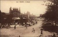 Bamako, le marché. – « Malinkés, Peulhs, Maures au marché. Ce marché n'est pas l'horrible halle en fonte, commandée en France, mais un beau bâtiment à pylônes ; le ciment armé, frère du torchis, se prête parfaitement à l'architecture soudanaise. Tout est d'un rose relevé de la tache noire des corps et des têtes et de la violence bleue des cotonnades, appelées « guinées ». Voici des barres de sel de Mauritanie que compissent des chiens errants non moins ignoble que les chiens chinois ; voici des anneaux de cheville en argent, en aluminium, des bagues d'or, convoités par les moussous (Noires, concubines des Blancs), du gingembre, des coquillages, des cosmétiques, des boules de beurre végétal, à l'odeur infecte, des colliers d'exportation, des fichus de tête » (1). Le marché central de Bamako, aussi appelé marché rose, a été partiellement détruit par un incendie en 1993. Il a depuis été reconstruit. Source : (1) Morand, Paul, A.O.F. de Paris à Tombouctou, Paris, Flammarion, 1928.