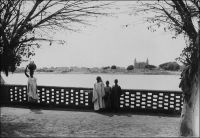 Mopti, vue sur la mosquée. – La grande mosquée de Mopti, appelée mosquée de Komoguel, fut érigée entre 1936 et 1943 sur le site d'une mosquée antérieure, elle-même bâtie en 1908. L'édifice réalisé sous la direction des maçons de Djenné présente de nombreuses similitudes avec la mosquée de cette ville. Construite en briques de terre et recouverte de banco, elle devait partiellement changer d'aspect quand ce revêtement fut remplacé par du ciment, lequel permettait de s'affranchir des opérations annuelles de réfection nécessitées par le banco, à l'occasion d'une restauration datant de 1978. Mais cette opération, employant des matériaux et des techniques inadaptés, avait fragilisé l'édifice. Une récente réhabilitation, empruntant des savoir-faire traditionnels, et notamment l'emploi d'un enduit réalisé à base de terre et de balle riz appelé « banco pourri »,  lui a rendu son aspect originel. - En 1947, époque à laquelle fut prise cette photo, la ville de Mopti est le chef-lieu d'un vaste cercle de 67 300 km2, qui compte une population de « 71 Européens, 16 Américains, 97 Libanais et 450 000 Africains » (1). Source : (1) Guid'AOF, Dakar, 1948.
