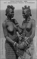 Jeunes femmes « Sourhaï » de Tombouctou. – « Les femmes [de Tombouctou] sont effrontées et habituées à servir, à exploiter l'étranger, à calmer le jeûne de générations de voyageurs. Elles descendent des anciennes courtisanes de Tombouctou, célèbres par leur culture et leurs appâts sociables. Déjà en 1350, Ibn Batonta, voyageur arabe, remarquait avec indignation qu'ici « les femmes recevaient des hommes sans que les maris en prissent ombrage ». On reconnaît là déjà la facilité des mœurs des Noirs. C'est que Tombouctou, s'il est l'Islam, n'est pas l'Islam pur » (1). - Cette photo fait partie du travail du célèbre photographe et éditeur dakarois Edmond Fortier (1862-1928) à qui l'on doit une somme importante de clichés sur l'Afrique de l'Ouest en général et sur le Soudan et le Sénégal en particulier ; il a publié en tout 3300 clichés originaux. M. Fortier tenait boutique et vivait avec ses deux filles blondes et son boy Seydou Traoré, à l'angle de la rue Dagorne et du boulevard Pinet-Laprade. Source : (1) Morand, Paul, A.O.F. de Paris à Tombouctou, Paris, Flammarion, 1928.